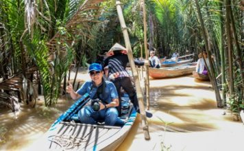 Du khách chèo thuyền trên kênh rạch